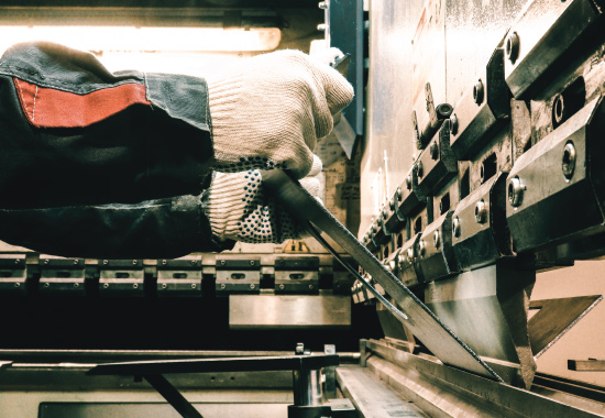 worker using machinery to form metal